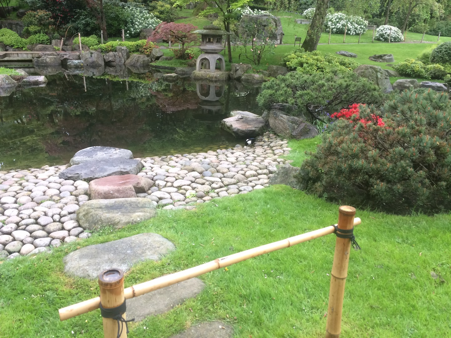Naturalistic rock pavers with the garden pond shore paved with large round river rocks.